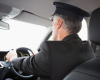A suited chauffeur at the steering of a vehicle
